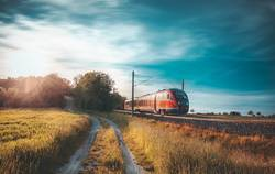 High-speed train moving through nature at sunset
