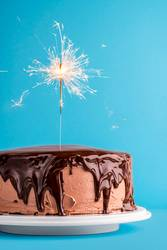Chocolate glazed birthday cake with a sparkler. New year cake