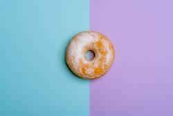 Single donut on blue-violet background. Minimalist flat lay