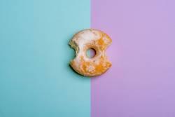 Bitten donut on blue-violet bicolored background