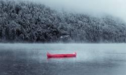 Rotes Kanu im winterlichem See