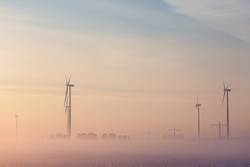 Wind generator at sunrise in the fog
