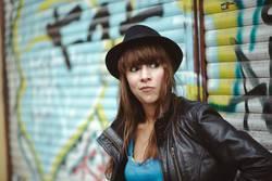 Frau mit Hut vor Graffiti schaut skeptisch zur Seite