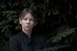 Strenge Frau mit schwarzer Bluse vor Nadelbäumen