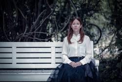 Frau mit weißer Bluse sitzt auf Parkbank