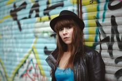 Coole Frau sitzt vor Graffiti und schaut in Kamera.