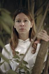 Ernste Frau mit weißer Bluse schaut durch Äste