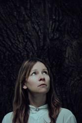 Portrait von ängstlicher Frau vor Baum schaut nach oben