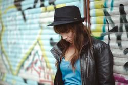 Frau steht vor Graffiti und schaut runter.
