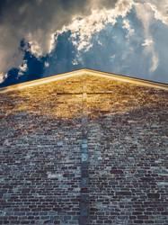 Fassade einer Kirche mit Kreuz und Wolkenhimmel