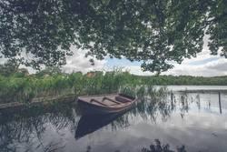 Small boat among green reed