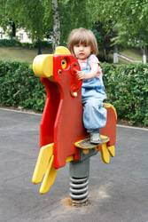Baby riding on hutches at the playground