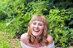 portrait of laughing woman with blond hair on summer background