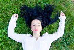 Beautiful brunette is lying on green grass