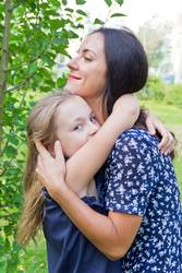 Kissing mother and daughter in summer