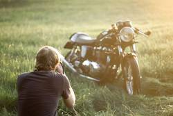 Young man observing Triumph thruxton motorcycle in the field.