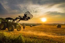 Landwirt und sein Traktor im Heufeld