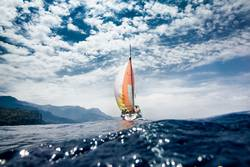 sailboat with colourful sail. Shot from inside the water.
