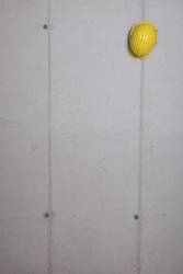 Yellow hard hat hanging on a grey concrete wall