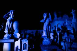 Two Angel statues at blue lightened tombstones during dawn