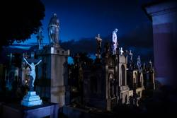 Jejus statues at blue lightened tombstones during dawn