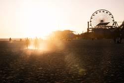 Silhouettes of people walking along Santa Monica pier