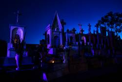 Blue and pink lightened tombstones with burning candles