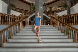Smiling woman with dog posing on steps