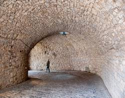 person walking through cobblestone arched tunnel road