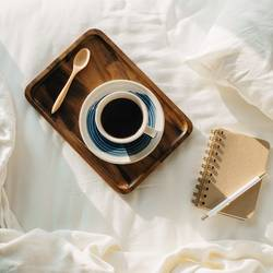 Coffee on wooden tray with notebook and pen on bed
