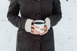 Woman's hands holding white enamel cup with hot drink