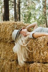 Blond woman in a hat lying hay stack, selective focus