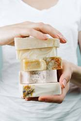 Woman's hands holding a stack of handmade soap