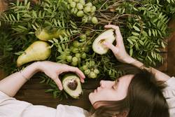 woman lying on wooden table holding grapes, pears and avocados