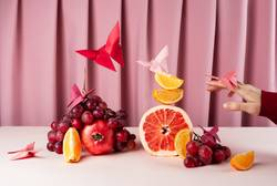 Various fruits on pink table with origame paper butterflies