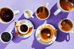 various cups with coffee and creamer on purple