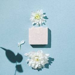 Minimalist flatlay of handmade soap with flowers and petals