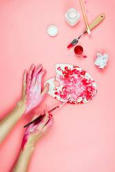 Woman's hands covered in paint and artist's supplies on pink