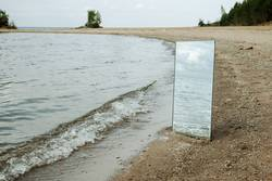 Mirror standing on a beach with waves reflection