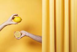 Two women's hands holding cut and whole lemons