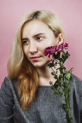 Floral portrait of female with blond hair on pink