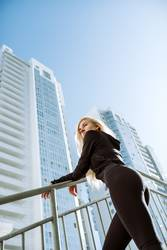 Female athlete standing in front of tall city buildings