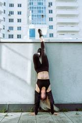 Young adult blond female doing a handstand outdoors