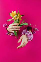 Hands through paper holding alstroemerias and flower bracelet