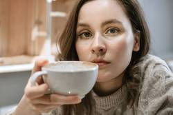 Young adult white woman with big cup of latte