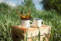 enamel mugs on a wooden box with splashing beverage