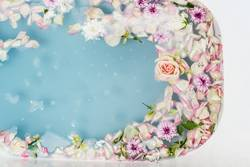 bath filled with blue bubble water, flowers and petals