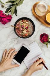 Flatlay of woman's hands holding smoothie bowl with laptop