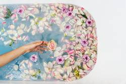bath filled with water, flowers and petals with woman's hand