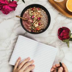 Woman's hands with notebook, smartphone and smoothie bowl